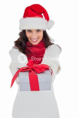 Festive brunette in santa hat giving gift