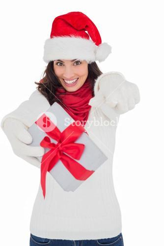 Excited brunette in santa hat giving gift