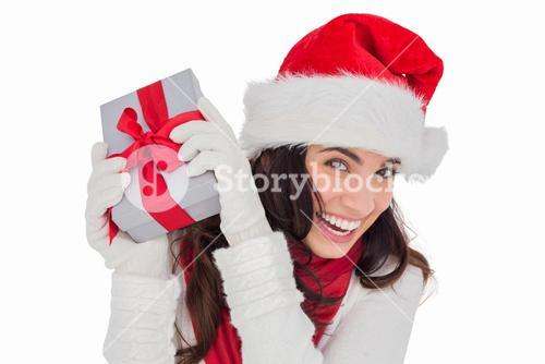 Happy brunette in santa hat holding gift