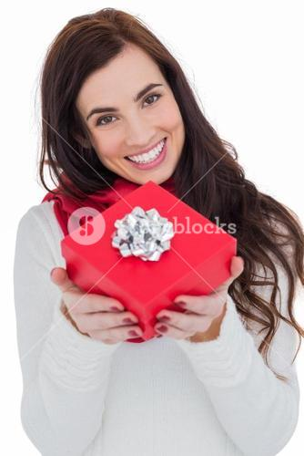Happy brunette showing red gift with a bow
