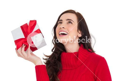 Happy brunette in red jumper hat showing a gift
