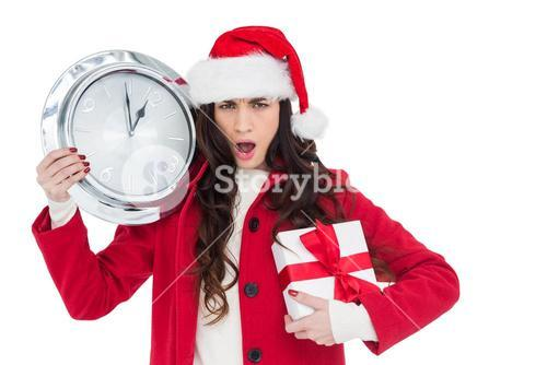 Surprised brunette holding a clock and gift