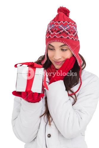 Content brunette in winter clothes holding gift