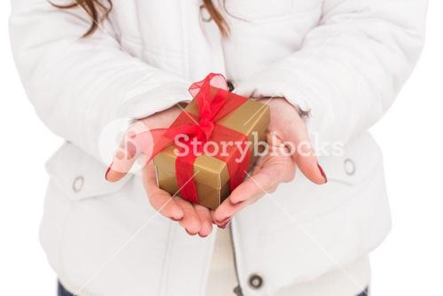 Woman in white coat holding gift