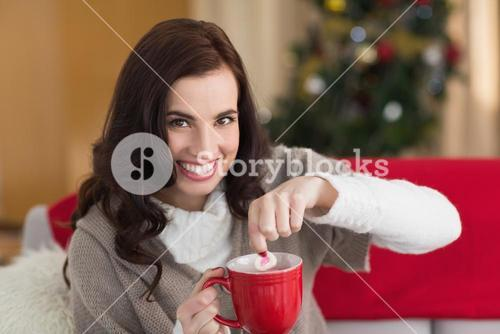 Brunette dunking marshmallow in hot chocolate at christmas