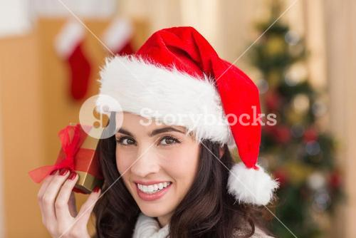 Festive brunette showing gift at chistmas