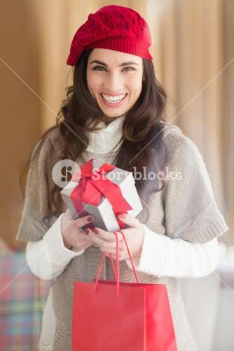 Happy brunette holding gift and shopping bags