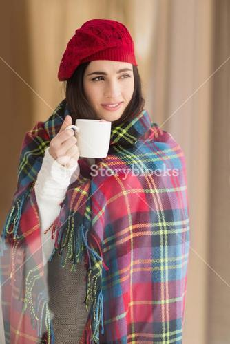 Brunette with cover holding mug and thinking