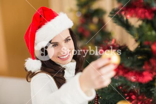 Happy brunette decorating a christmas tree