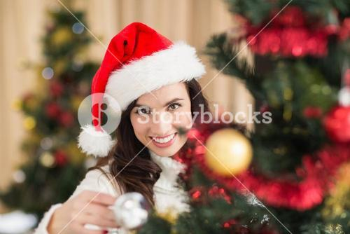 Beauty brunette decorating a christmas tree