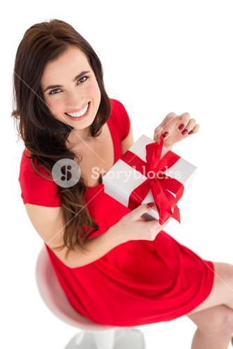 Smiling brunette sitting and opening gift