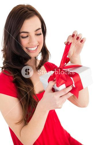 Happy brunette sitting and opening gift