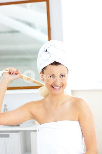 Lively woman washing her back smiling at the camera in the bathroom