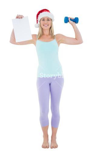 Festive fit blonde holding page and dumbbell