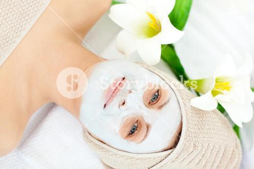 Smiling woman with white cream on her face looking at the camera