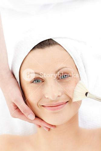 Smiling young woman receiving a beauty treatment