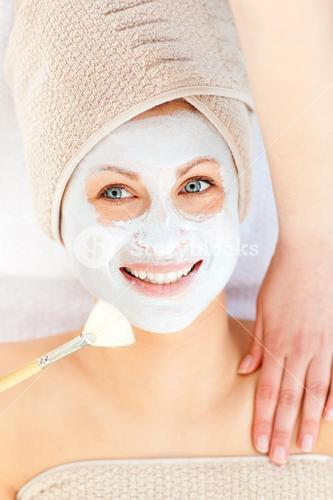 Radiant young woman having white cream on her face