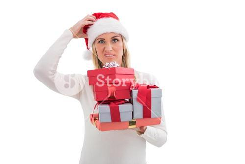 Confused blonde in santa hat holding gifts