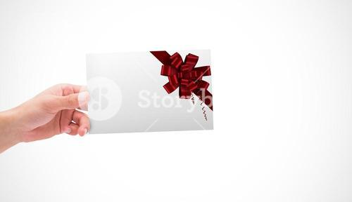 Composite image of hand holding card