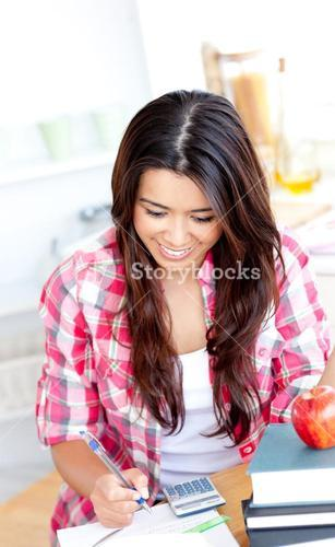 Merry female student doing math in the kitchen