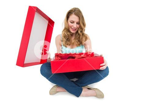 Pretty woman opening a gift smiling at it