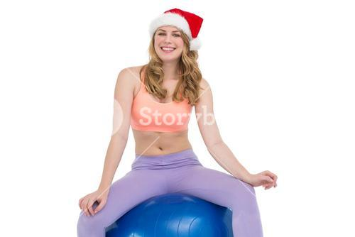 Smiling blonde woman sitting on exercise ball