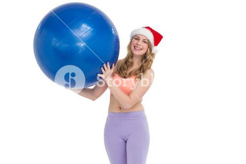 Smiling blonde woman holding exercise ball