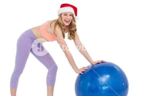 Festive blonde woman using exercise ball
