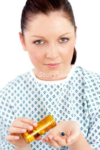 Dejected ill woman holding pills looking at the camera