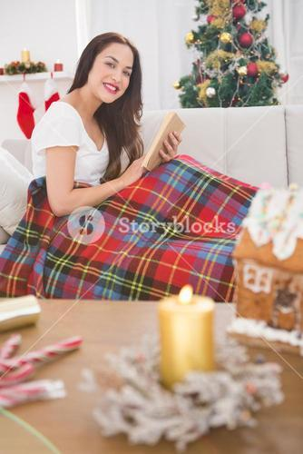 Smiling brunette reading on the couch with cover