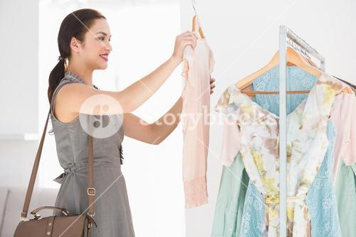Happy shopping brunette looking at shirt