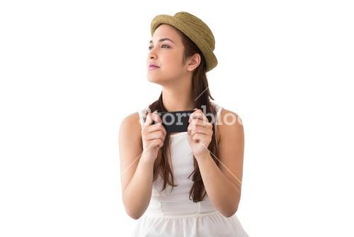 Happy brunette in hat holding phone