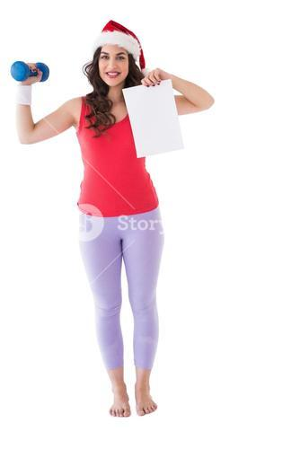 Festive athletic brunette holding page and dumbbell