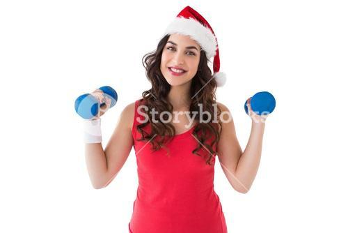Festive fit brunette holding dumbbells