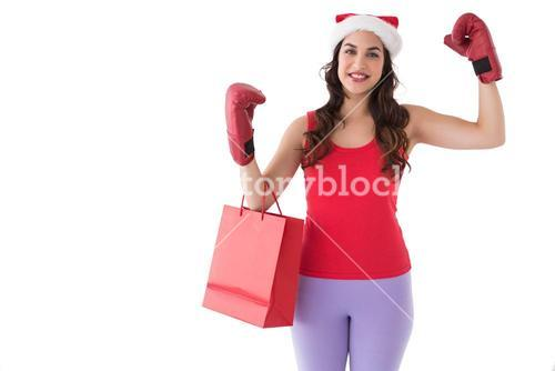 Festive brunette in boxing gloves with shopping bag