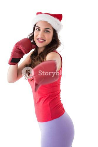 Festive brunette in boxing gloves punching