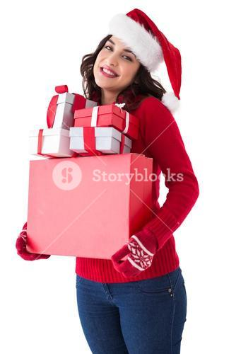 Happy brunette in santa hat holding many gifts