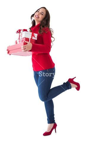 Happy brunette in winter clothes holding presents