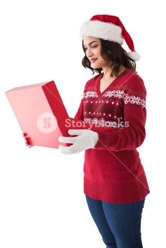 Festive brunette in winter clothes opening gift