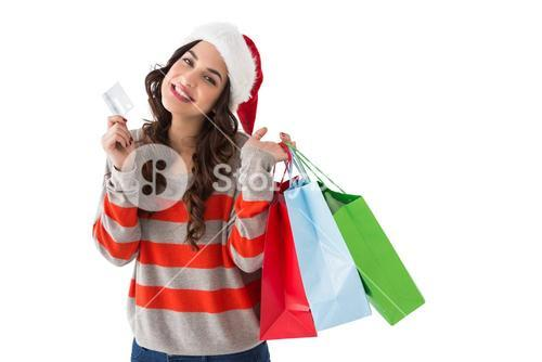Smiling brunette holding credit card and shopping bags