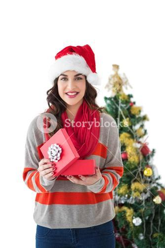 Festive brunette opening gift by the tree
