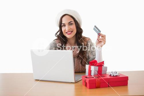 Pretty brunette shopping online with laptop