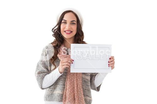 Brunette in winter clothes holding sale sign