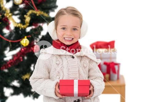 Festive little girl holding a gift