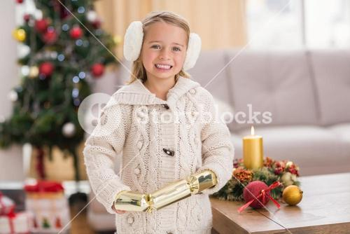 Festive little girl holding a cracker