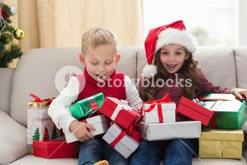 Festive siblings surrounded by gifts