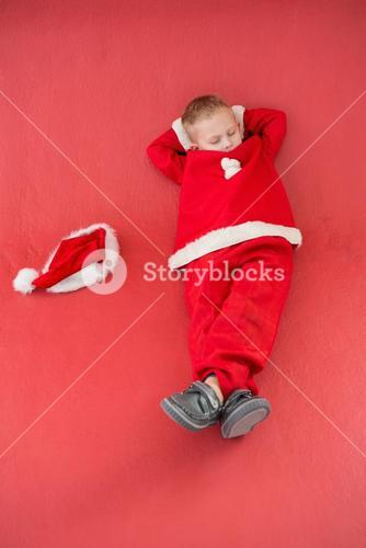 Little boy napping in santa costume