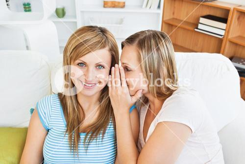 Portrait of two female friends telling secrets at home
