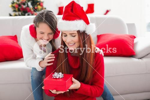 Festive mother and daughter with a christmas gift