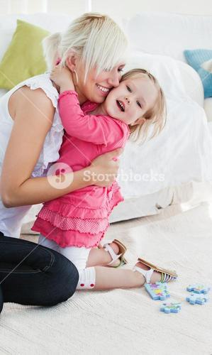 Cheerful little girl hugging her mother